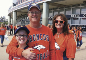 Klark Kindler, left, has been named the new athletic director at Meeker High School in addition to his continuing as the Cowboys' basketball coach. Kindler and his daughter Madison, left, and his wife, Jewell, right, are seen here at a Broncos game last year, something the whole family enjoys.