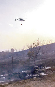 """A Bureau of Land Management helicopter with a water drop bucket was """"a really important tool"""" in fighting Thursday afternoon's 130-acre blast up County Road 7."""