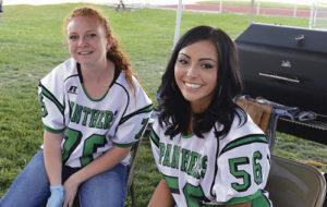 Savannah Nielsen and Breanne Baker served pulled pork prepared by Crandal Mergelman at Friday night's Rangely High School football game.