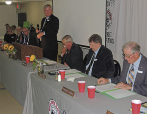 A full house of company officials and members of White River Electric Association filled the Fairfield Center for the WREA's annual Meeting of the Membership on Sept. 9. After being fed by the Meeker Lions Club, the company officials and members got down to business, first listening to WREA General Manager Alan Michalewicz (standing). Also at the head table are, from left to right, WREA Counsel Trina Zagar-Brown, and WREA board members Gary H. Dunham, Richard L. Parr, Hal W. Pearce, Michalewicz, Board President William H. Jordan and board members Stan Wyatt and Ronald K. Hilkey. Present but not in the photo is Richard R. Welle.