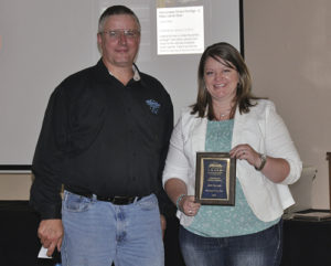 "Scott Jones, left, president of the Colorado OHV Coalition, presented Katelin Cook, right, the director of economic development for Rio Blanco County, with an ""Award of Special Recognition,"" honoring Rio Blanco for the high quality of its Wagon Wheel Trails Program. The award was presented at an OHV workshop this summer."