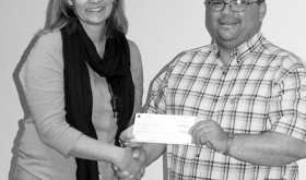 Chevron representative Chris Archuleta, a Meeker resident and school parent, presents Meeker High School Principal Amy Chinn with a $250 check for the high school FFA program.