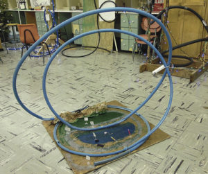 Kale Burke's No. 2-ranked Blue Lagoon Joy Ride marble coaster, in the foreground, had a transferred energy loss of 70 percent. Although he used the action of a sawed-off BB gun to start his marble (from the bottom) with elastic energy, his marble transferred a lot of energy, having to go up two big loops. In the background: on the left, Allie Willey's No. 6-ranked Loopty Loop blue coaster with lights; in the middle, Kyler Bland's pragmatic black tubing coaster; and, on the right, Ellie Anderson's lit-up pipe insulation coaster.