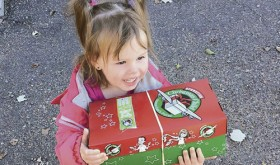 Bethanie, the 2-year-old daughter of Rangely Christian Church's Pastor Shannon and Krystal Brumfield, proudly carries in one of the Operation Christmas Child boxes.