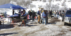 "Above, friends and family of the Mike and Kathy Sizemore help prepare lunch or gather around to wait for the food during the fifth annual ""I Ride With James"" Snowmobile and Poker Run on Sunday up County Road 8 at Lost Deer Trailhead. More than 200 snowmobile riders took part this year and the winner of the grand prize, which was a Polaris 120 child's snowmobile, in photo below, was Roger Foster."