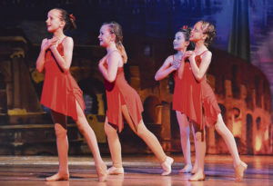 "Third- and fourth-grade jazz dancers perform to ""That's Amore."" From left to right: Rhiwan Williams, Eva Scritchfield, Natalie Knight and Alli Sanders."