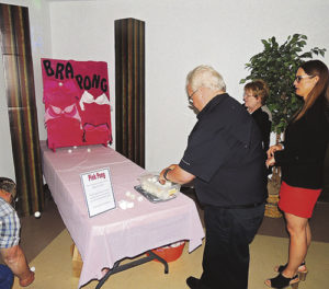 Cindy Welle, center, and Trina Zagar-Brown, right, watch as Dick Welle tries his luck at bra pong, one of the games at the Forks & Flavors fundraiser event for a new 3-D mammography machine for Pioneers Medical Center. The idea is to bounce a ping pong ball off the table and into one of the cups of one of bras against the wall. It is not an easy feat, as most of those who tried the game found out.