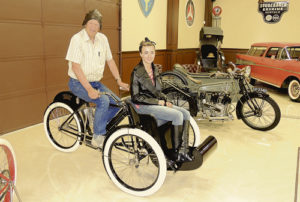 Bud Striegel, owner of the newly opened Rangely Automotive Museum, put employee Kelsey Peters in the passenger seat of this 1907 Indian Tri-car Sunday, one of the many motorcycles and automobiles on display at the museum. The museum will hold its grand opening May 28. The museum is open on Thursdays, Fridays, Saturdays and Sundays at the intersection of Stanolind and Highway 64.