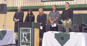 Officials on the podium at Saturday afternoon's Rangely High School Commencement exercises, held in the gym at RHS, were, from left to right: Athletic Director Crandal Mergelman, Rangely High School Principal K.D. Bryant, Counselor Dixie Fielder, special guest speaker and baseball/football coach Paul Fortunato and District Superintendent Matt Scoggins.