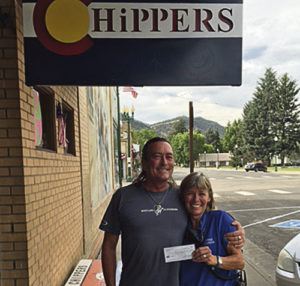 Ted Relihan, left, a Meeker artist at Mustang Studio, celebrated his 55th birthday by collaborating with Chipper's Bar. For every drink bought on his birthday, Larin Crase and Danielle Feola (owners of Chippers) donated 55 cents toward the Meeker Animal Shelter. Meeker Animal Control Officer Laurel Haney, right, will use the money for food and spay and neutering of the animals in the shelter. The collaboration brought in $200 for the shelter. Left is a photo of Ted Relihan and Laurel Haney at Chippers exchanging the check.