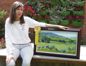 """Meeker artist Pat Sheeran-Daggett sits in Meeker Public Library's new courtyard with her """"People's Choice"""" award-winning plein air art. Her piece, titled """"View of the Valley,"""" was painted from Meeker's Ute Park and depicts the David Smith Ranch looking across the White River and up Flag Creek. The award came with $300 sponsored by the Elk Mountain Inn. Her award was one of the six monetary awards given at the Meeker Chamber of Commerce's Plein Air Meeker 2016 competition, which involved 15 artists, 50 works and 12 art buyers."""