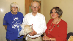"""From left, Meeker's Sue Hicken, who tracked down the names of survivors, and Rio Blanco County Coroner Albert Krueger, MD, presented niece Anna Lynn Vogel with the skull of her uncle, Herman """"Hermie"""" Leroy Park, at a small gathering in Meeker on July 15, reuniting Park with a member of his family after 86 years. The skull was transported to Lamoni, Iowa, to be buried."""