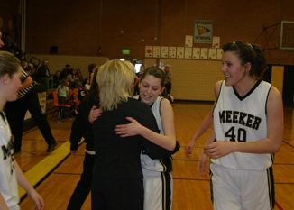 Elissa McLaughlin hugged coach Hallie Blunt as Rebecca de Vergie, right, and fellow teammates celebrated at the conclusion of Saturday's come-from-behind victory in the first round of districts. The Lady Cowboys continue on to the next round Friday at Rangely.