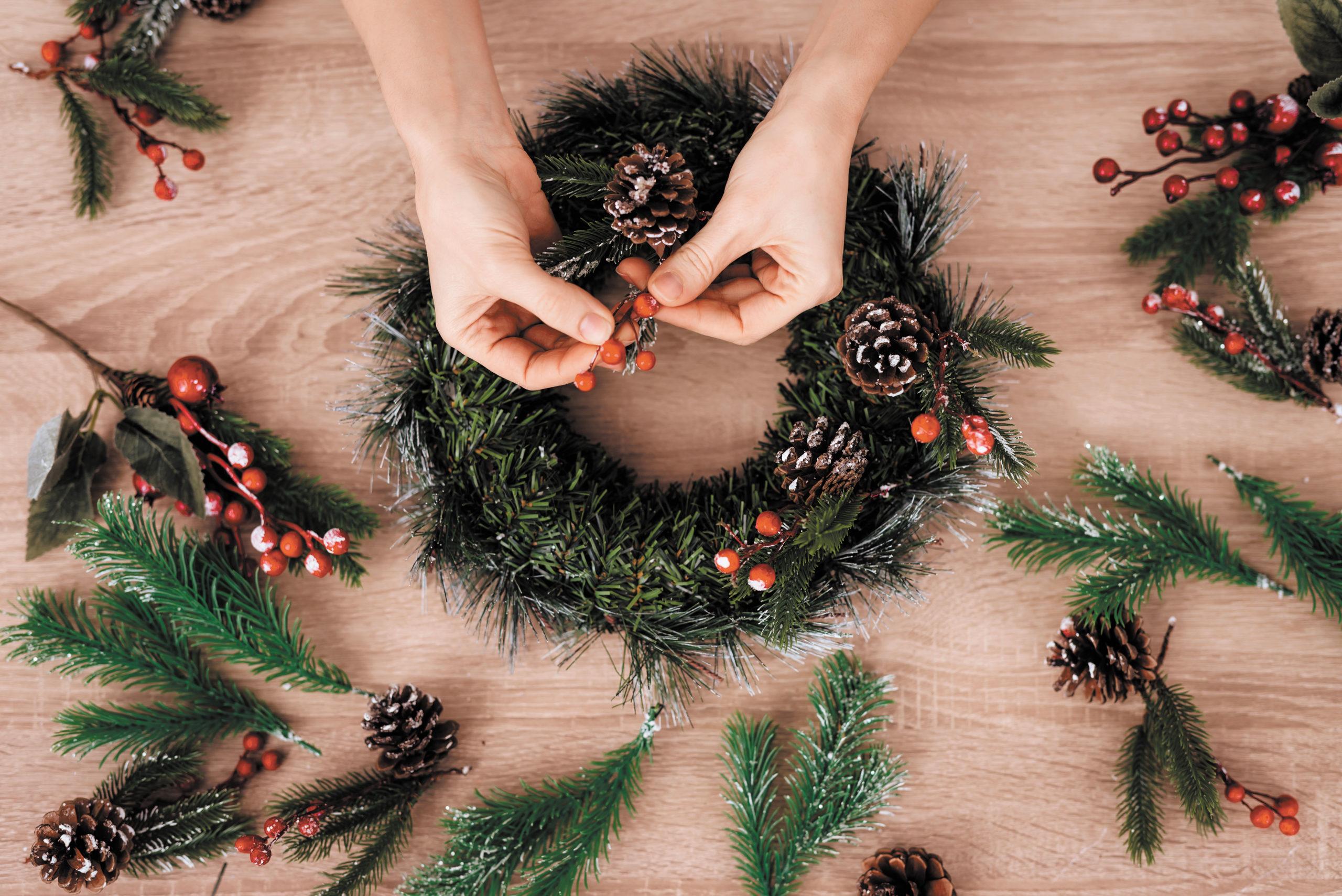 Woman Making Christmas Wreath for Xmas Holidays.